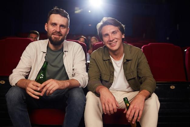 Vooraanzicht portret van twee mannelijke vrienden glimlachend en houden bierflesjes camera kijken tijdens het kijken naar film in bioscoop, kopie ruimte
