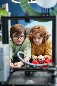 Vooraanzicht portret van twee schooljongens die naar 3d-printer kijken tijdens techniekles op moderne school, kopieer ruimte