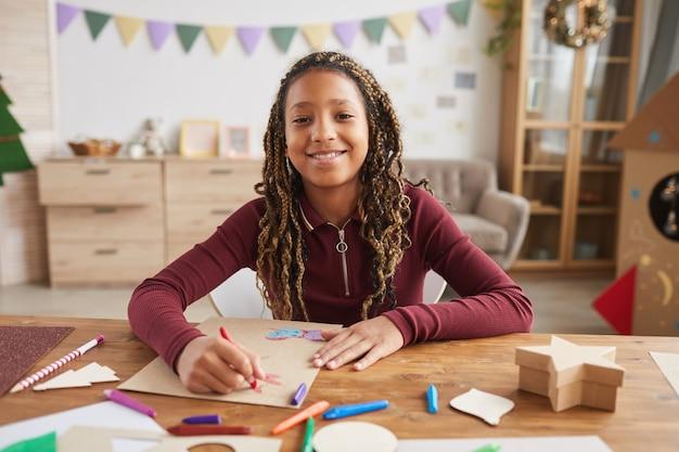 Vooraanzicht portret van vrolijk afrikaans-amerikaans meisje camera kijken terwijl u geniet van tekening zittend aan een bureau in interieur, kopieer ruimte