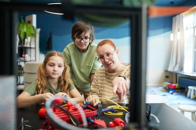 Vooraanzicht portret van vrouwelijke leraar wijzend op 3d-printer tijdens engineering en robotica klasse op moderne school, kopieer ruimte