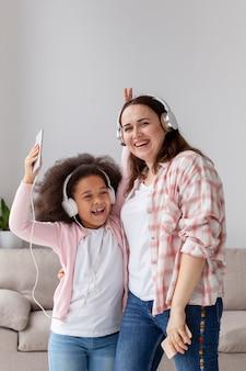 Vooraanzicht positieve moeder en dochter poseren