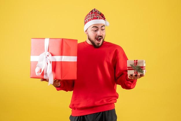 Vooraanzicht presenteert jonge mannelijke kerstcadeautjes op gele achtergrond
