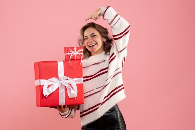 Vooraanzicht presenteert jonge vrouwelijke kerstcadeautjes