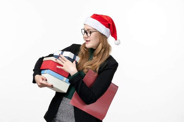 Vooraanzicht presenteert jonge vrouwelijke vakantie houden op witte muur cadeau boek nieuwjaar