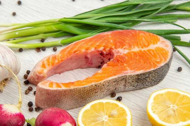 Vooraanzicht rauw vleesplak met greens radijs en knoflook op witte achtergrond voedsel dierlijke rib schotel maaltijd vis