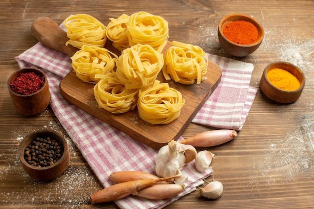 Vooraanzicht rauwe deeg bloem gevormde pasta met kruiden op een houten ruimte