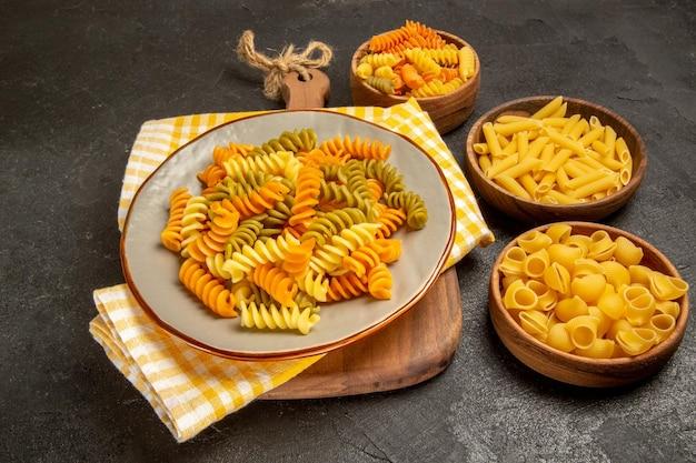 Vooraanzicht rauwe italiaanse pasta anders gevormd in bruine platen op grijze ruimte
