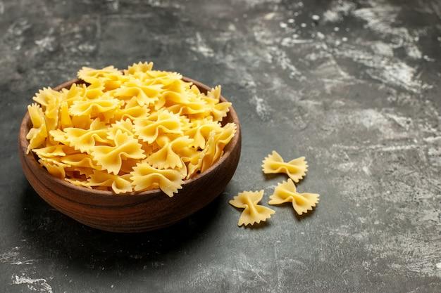 Vooraanzicht rauwe italiaanse pasta binnen plaat op de donkergrijze kleurenfoto maaltijd deeg eten keuken