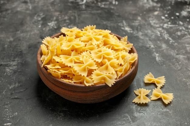 Vooraanzicht rauwe italiaanse pasta binnen plaat op donkergrijze kleurenfoto maaltijd deeg veel eten