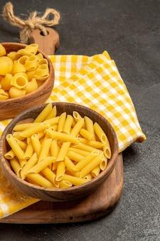 Vooraanzicht rauwe italiaanse pasta in bruine borden op grijze ruimte