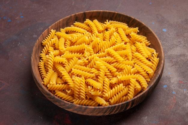Vooraanzicht rauwe italiaanse pasta in houten dienblad op donkere ruimte