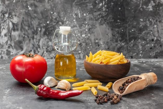 Vooraanzicht rauwe italiaanse pasta met eieren tomaat en olie op lichtgrijze achtergrond deeg maaltijd eten pasta keuken