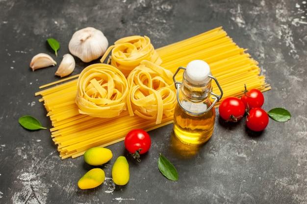 Vooraanzicht rauwe italiaanse pasta met knoflook en tomaten op lichtgrijze keukenmaaltijdkleurvoedsel