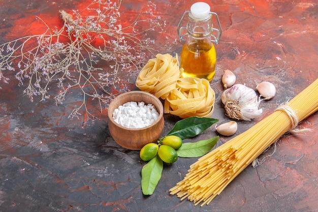 Vooraanzicht rauwe pasta met olie en knoflook op donker oppervlak rauw deeg pastavoedsel
