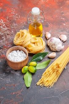 Vooraanzicht rauwe pasta met olie en knoflook op donkere oppervlak rauwe deeg pasta