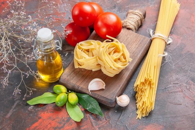 Vooraanzicht rauwe pasta met olietomaten en knoflook op donker oppervlak rauw pastadeeg