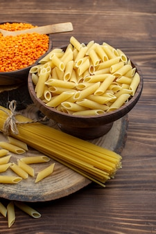 Vooraanzicht rauwe pasta met oranje linzen op bruin oppervlak