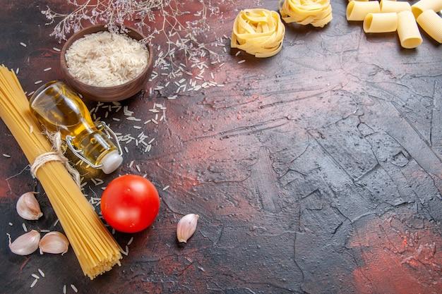 Vooraanzicht rauwe pasta met verschillende ingrediënten op donkere oppervlak deeg pasta rauw