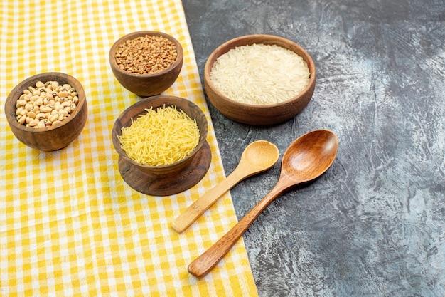 Vooraanzicht rauwe rijst met bonen in kleine potten op een lichtgrijze achtergrond rauwkost maaltijd foto kleur ingrediënt