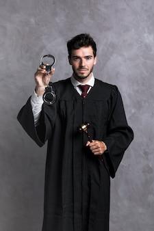 Vooraanzicht rechter in badjas met handboeien en hamer