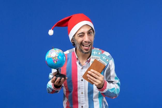 Vooraanzicht regelmatige man met kaartjes en globe op blauwe vloer kleur vakantie nieuwjaar