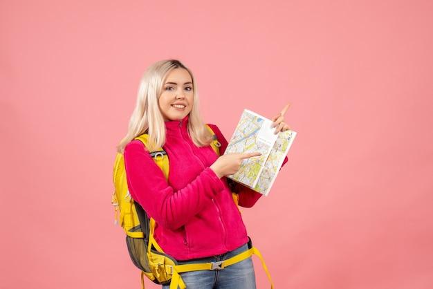 Vooraanzicht reiziger vrouw met gele rugzak met kaart naar rechts wijzend