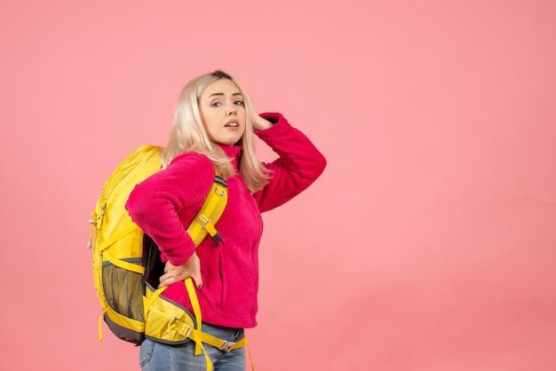 Vooraanzicht reiziger vrouw met rugzak hand op een taille zetten