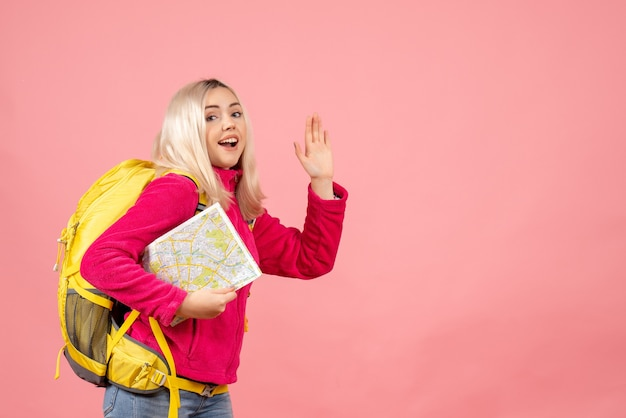 Vooraanzicht reiziger vrouw met rugzak met kaart zwaaiende hand