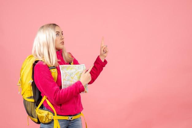 Vooraanzicht reiziger vrouw met rugzak wijzende vinger omhoog bedrijf kaart