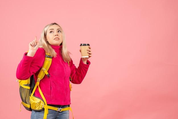 Vooraanzicht reiziger vrouw met rugzak wijzende vinger omhoog bedrijf koffiekopje