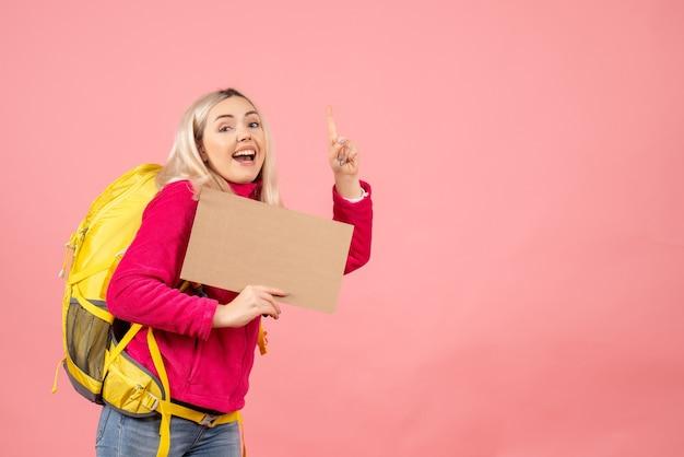 Vooraanzicht reiziger vrouw met rugzak wijzende vinger plafond houden karton