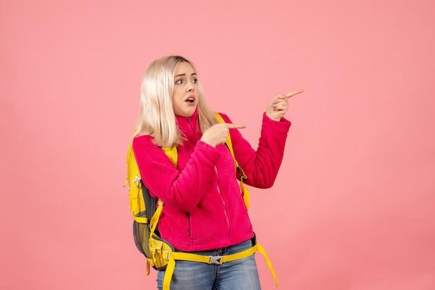 Vooraanzicht reizigersvrouw in vrijetijdskleding die rugzak draagt die naar rechts wijst