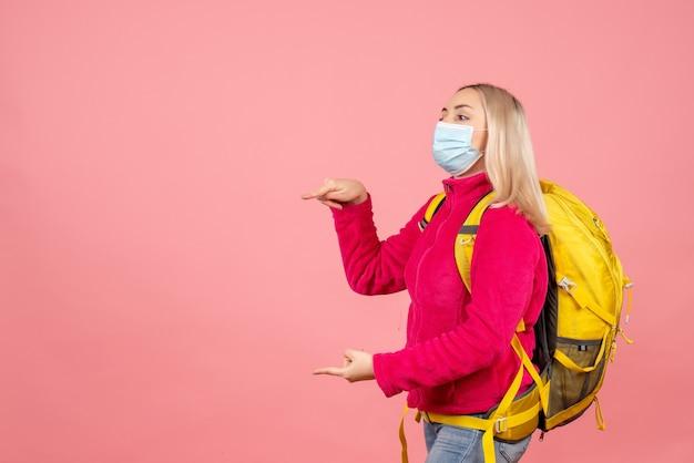 Vooraanzicht reizigersvrouw met gele rugzak die naar links richtend masker draagt