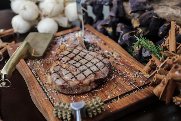 Vooraanzicht rib steak met kaneel knoflook en een bijl op een stand