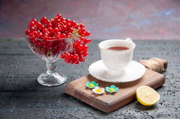 Vooraanzicht rode aalbes in een glas een kopje thee op een snijplank en een schijfje citroen op donkere achtergrond