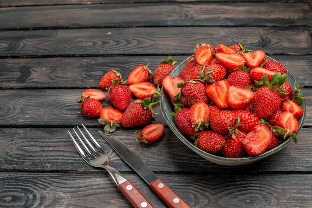 Vooraanzicht rode aardbeien gesneden en hele vruchten op donkere houten rustieke bureau zomer kleur boom sap berry wild