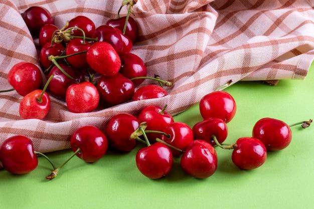 Vooraanzicht rode kers met een keukenhanddoek op lichtgroen