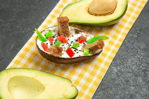 Vooraanzicht romige avocado's met verse avocado op donkergrijze ruimte