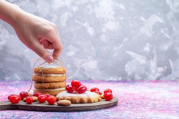 Vooraanzicht romige sandwichkoekjes met rode kornoeljes die door vrouwtje op helder worden bekeken