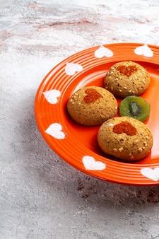 Vooraanzicht ronde suikerkoekjes binnen plaat op het witte oppervlak koekjes koekje suiker zoete cake
