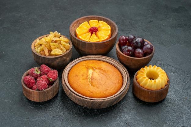 Vooraanzicht ronde taart met fruit en rozijnen op donkergrijze achtergrond, zoete koekjestaart, fruitbessen