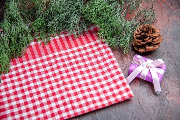 Vooraanzicht rood en wit geruit tafelkleed dennenboom takken dennenappel kerstcadeau op donkerrode achtergrond