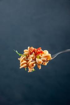 Vooraanzicht rotini pasta op vork op donkere geïsoleerde oppervlakte vrije ruimte