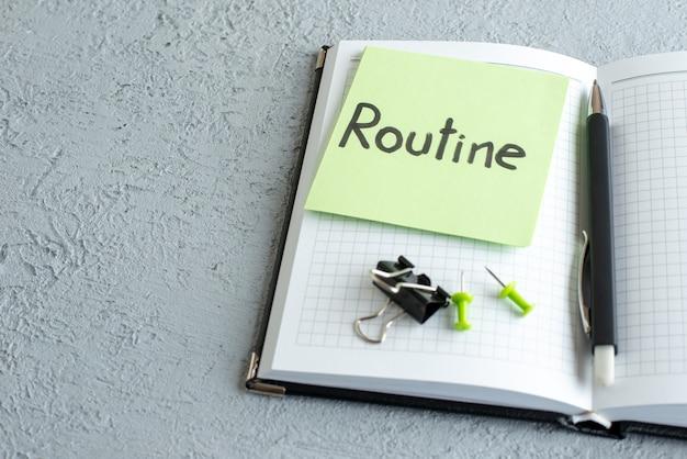 Vooraanzicht routine geschreven nota over groene sticker met blocnote en pen op witte achtergrond