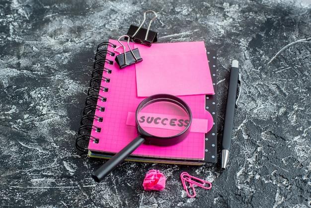 Vooraanzicht roze blocnote met pen meer magnifier en succesnota over grijze achtergrond