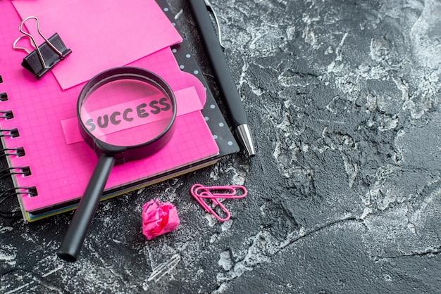 Vooraanzicht roze blocnote met pen vergrootglas en succesnota over grijze achtergrond