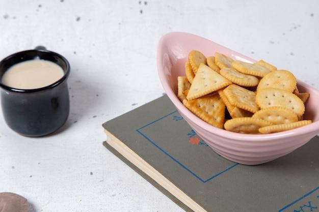 Vooraanzicht roze plaat met crackers en chips, samen met melk op grijs