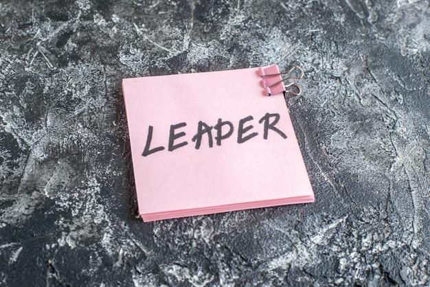 Vooraanzicht roze sticker met leider geschreven notitie op grijze ondergrond job business school college kleurenfoto kantoor