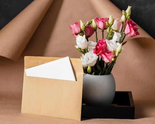 Vooraanzicht rozen in vaas arrangement met envelop