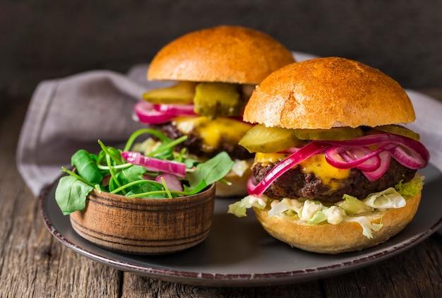 Vooraanzicht rundvleesburgers met augurken op snijplank